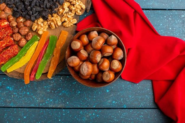 Vista dall'alto di nocciole intere fresche con noci e gelatine sulla scrivania blu Foto Gratuite