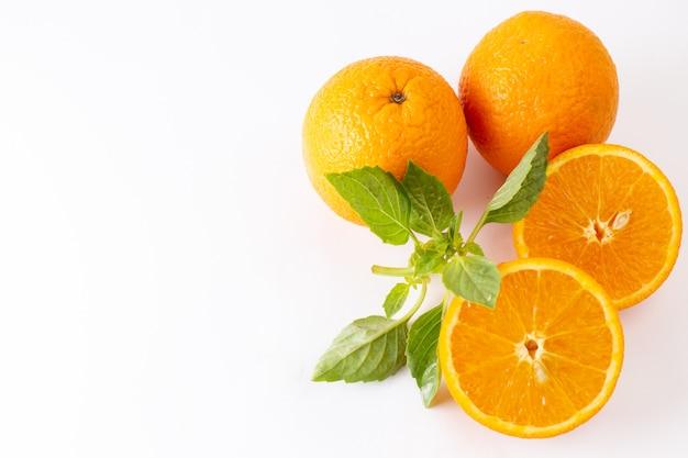 トップビューフレッシュオレンジ全体のジューシーで酸っぱい、白い背景の緑の葉と酸っぱいエキゾチックな柑橘系色の果物 無料写真