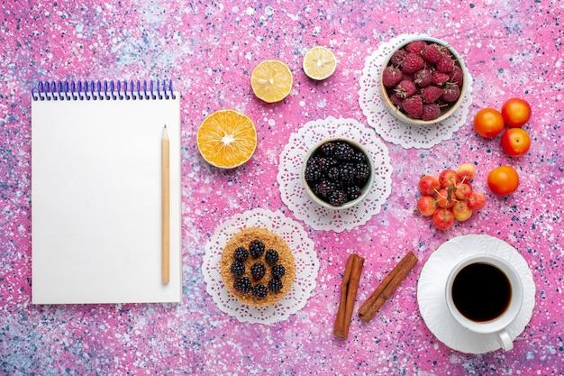 ピンクの机の上に小さなケーキとお茶と新鮮な野生のベリーラズベリーとブラックベリーの上面図。 無料写真