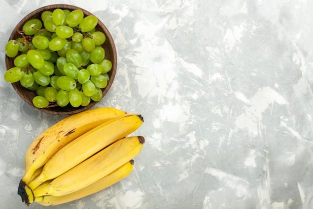平面図新鮮な黄色のバナナまろやかでおいしい果物とブドウが明るい白い机の上に 無料写真