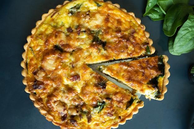 Top view freshly bake leek bacon spinach quiche on dark background Premium Photo