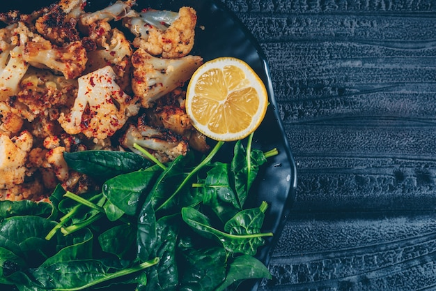 Top view fried cauliflower in plate with greens and lemon on dark wooden background. horizontal Free Photo
