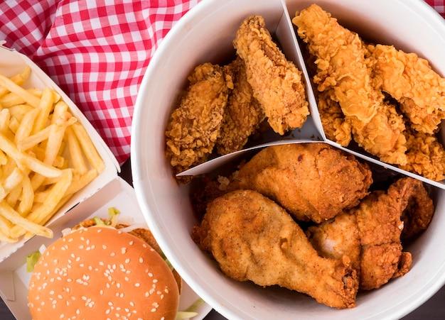 Vista dall'alto secchio di pollo fritto con hamburger e patatine fritte Foto Gratuite