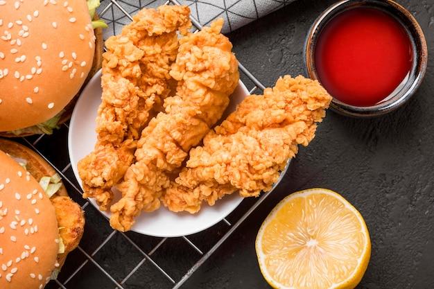 Vista dall'alto pollo fritto e hamburger sul vassoio con salsa e limone Foto Gratuite