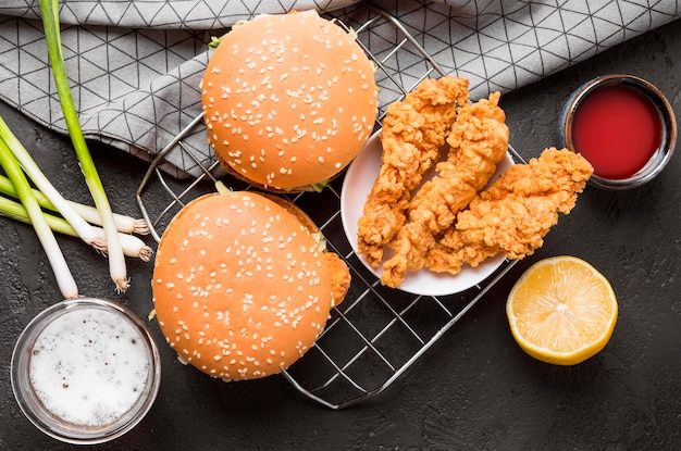 Top view fried chicken and burgers on tray with sauces Free Photo