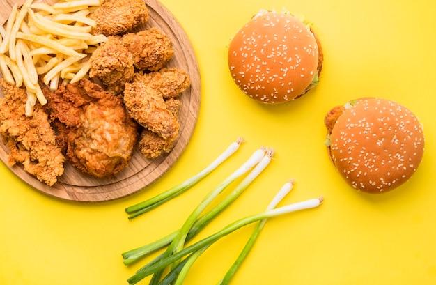 Vista dall'alto pollo fritto e hamburger con patatine fritte e cipolla verde Foto Gratuite