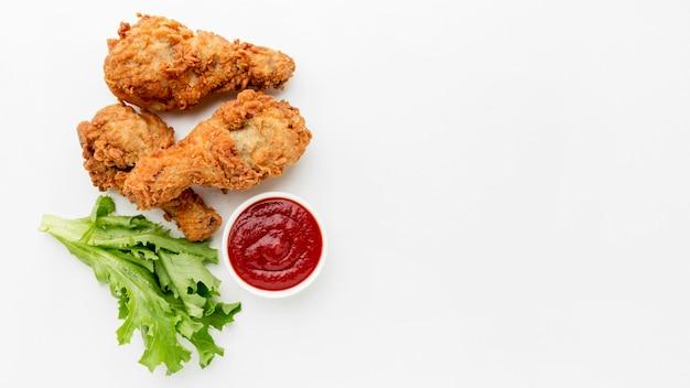 Вид сверху жареные куриные голени с кетчупом и копией пространства Premium Фотографии