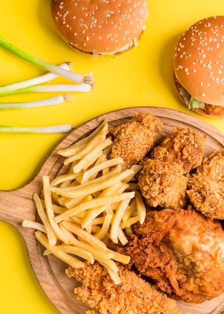 Vista dall'alto pollo fritto e patatine fritte con hamburger e cipolle verdi Foto Gratuite