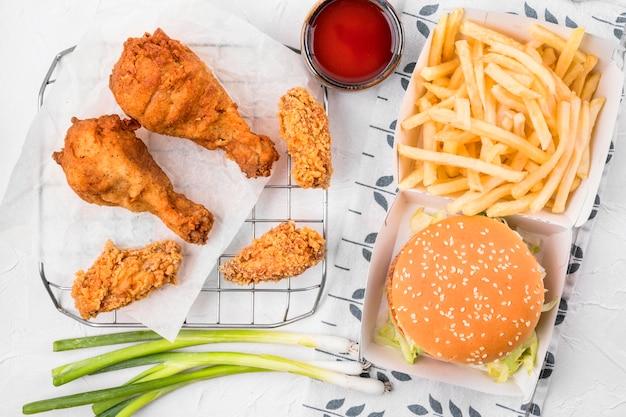 Vista dall'alto pollo fritto sul vassoio con patatine fritte Foto Gratuite