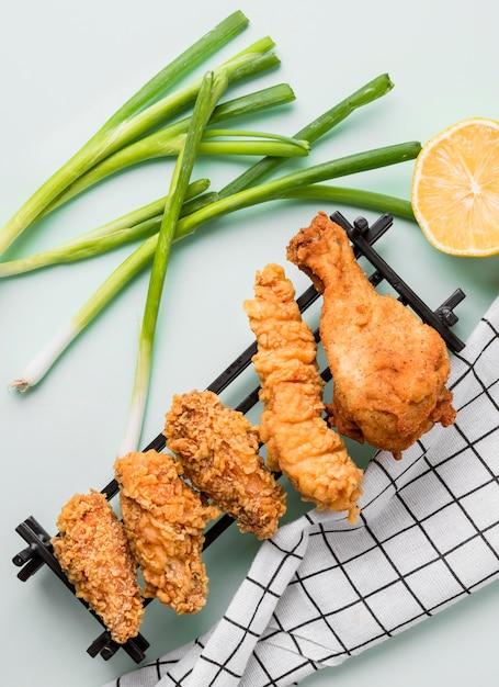 Vista dall'alto pollo fritto sul vassoio con cipolle verdi, limone e canovaccio Foto Gratuite