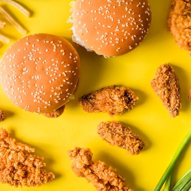 상위 뷰 튀긴 닭 날개와 감자 튀김과 햄버거 프리미엄 사진