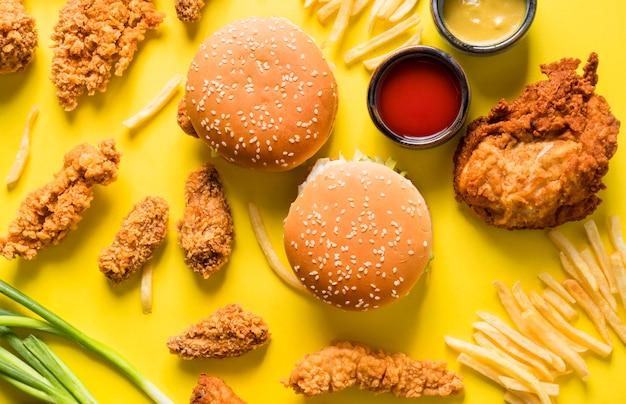 소스와 함께 튀긴 닭 날개, 햄버거 및 감자 튀김 상위 뷰 프리미엄 사진