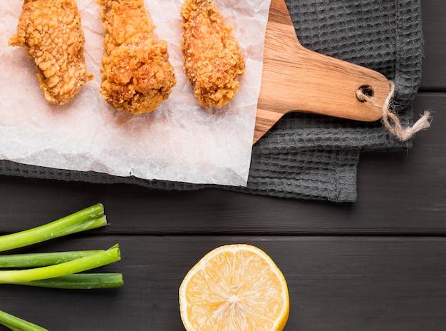 Вид сверху жареные куриные крылышки на разделочной доске с лимоном и зеленым луком Premium Фотографии