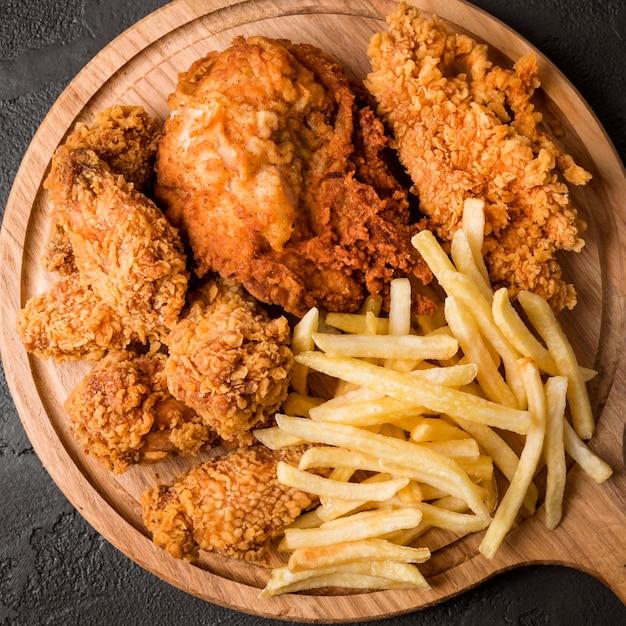 Жареный цыпленок с картофелем фри на разделочной доске, вид сверху Premium Фотографии