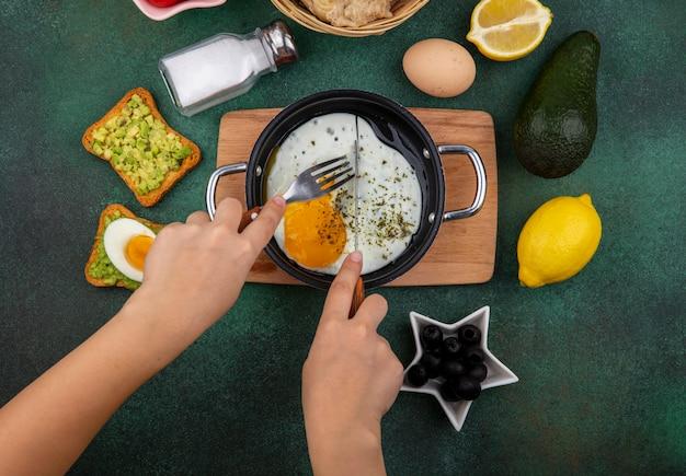 Vista dall'alto di uovo fritto in padella su tavola di legno kitche con fette di pane tostato con polpa di avocado olive nere su verde Foto Gratuite