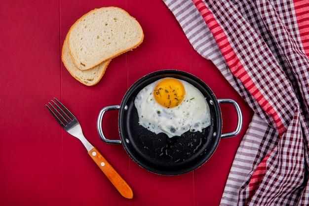 Vista dall'alto di uovo fritto in padella con fette di pane e forchetta sul rosso Foto Gratuite