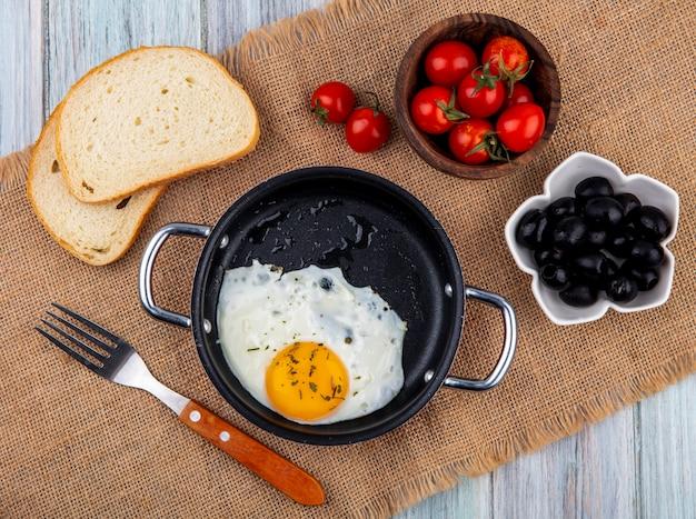 Vista dall'alto di uovo fritto in padella con forchetta e ciotola di fette di pane e pomodoro su tela di sacco e legno Foto Gratuite