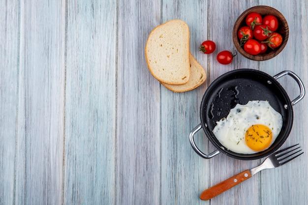 Vista dall'alto di uovo fritto in padella con forchetta e ciotola di fette di pane e pomodoro su legno con spazio di copia Foto Gratuite