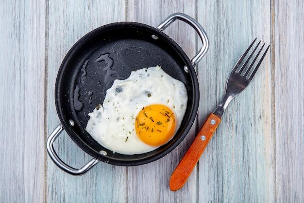 Vista dall'alto di uovo fritto in padella con forchetta su legno Foto Gratuite