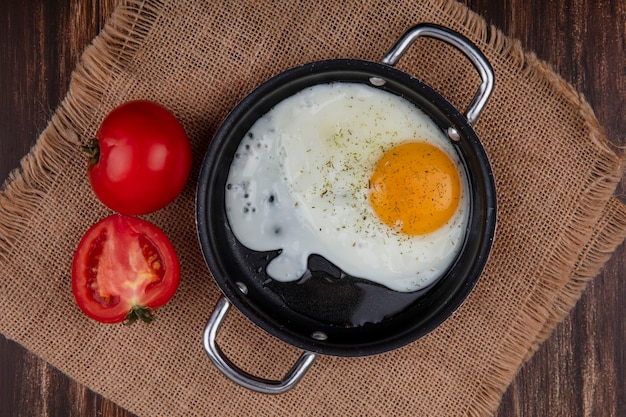 Top view fried egg in a pan with tomatoes on a beige napkin  on a wooden background Free Photo