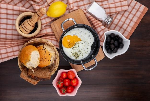 Vista dall'alto di uovo fritto in padella sul bordo di cucina in legno con un bcuket di pane olive nere pomodori Foto Gratuite