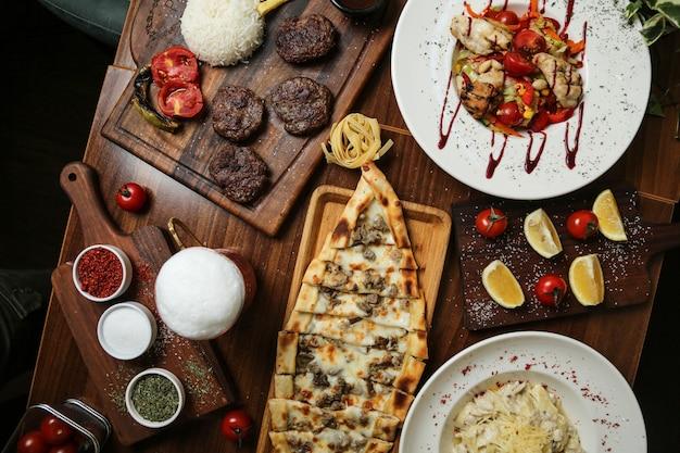 Вид сверху жареные мясные котлеты с салатом пиде и специями на столе Бесплатные Фотографии