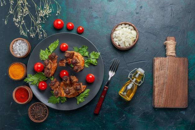 Vista dall'alto fette di carne fritte con olio d'oliva e condimenti sul pasto salutare di carne di cibo vegetale scrivania blu scuro Foto Gratuite