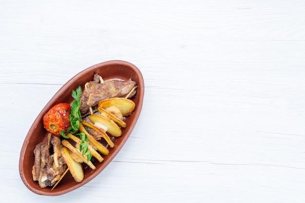 Vista dall'alto di carne fritta con verdure e prugne al forno all'interno del piatto marrone sullo scrittorio luminoso, cena del piatto di carne del pasto del cibo Foto Gratuite