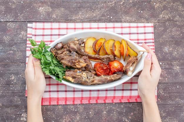 Vista dall'alto di carne fritta con verdure e prugne al forno all'interno della piastra sullo scrittorio rustico marrone, verdura cena piatto di carne pasto cibo Foto Gratuite