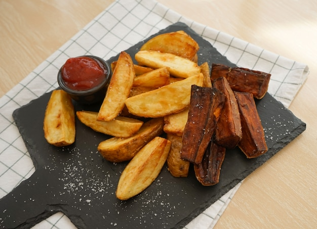 Top view of fried potatoes and baked sweet potato on black slate plate severed with tomato sauce Premium Photo