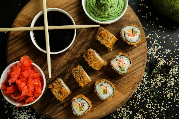 Вид сверху жареные суши роллы на подставке с имбирным соевым соусом и васаби с палочками для еды Бесплатные Фотографии