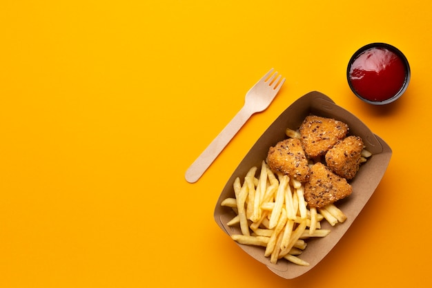 Top view fries and crispy in a box with sauce Free Photo
