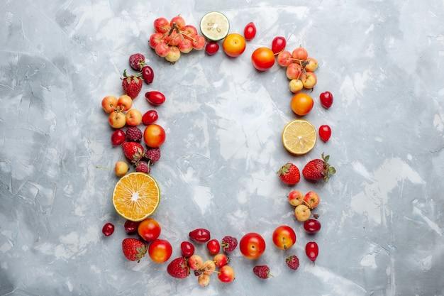 Вид сверху фруктовая композиция лимоны, сливы и вишня, выложенные на белом столе, спелые фрукты, свежий мягкий витамин Бесплатные Фотографии