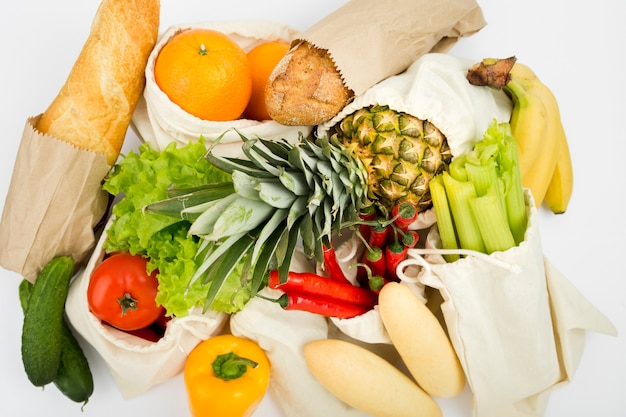 Top view of fruit and vegetables in reusable bags with bread Free Photo
