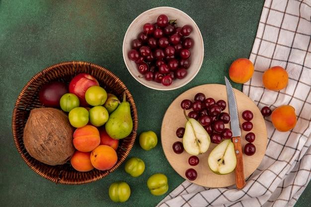 Vista dall'alto di frutti come ciliegie pera cocco prugna albicocca pesca con coltello nel cestello e sul tagliere su plaid panno su sfondo verde Foto Gratuite