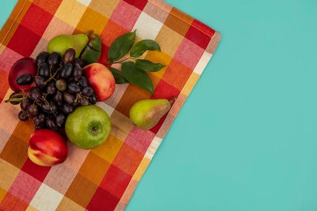 Vista dall'alto di frutta come uva pesca mela pera con foglie su un panno plaid e sfondo blu con spazio di copia Foto Gratuite
