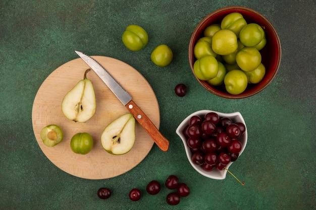 Vista dall'alto di frutta tagliata a metà pera e prugna con coltello sul tagliere e ciotole di ciliegia e prugna su sfondo verde Foto Gratuite