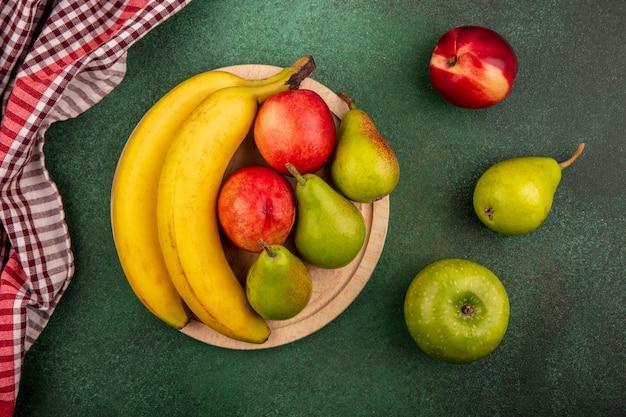 Vista dall'alto di frutta come banana pera pesca sul tagliere con mela e panno plaid su sfondo verde Foto Gratuite