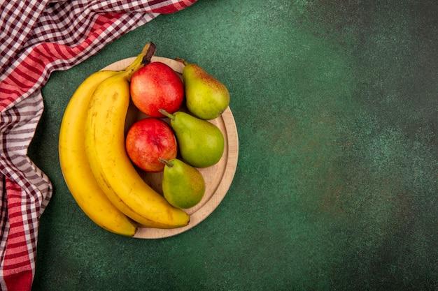 Vista dall'alto di frutta come banana pera pesca sul tagliere con panno plaid su sfondo verde con spazio di copia Foto Gratuite