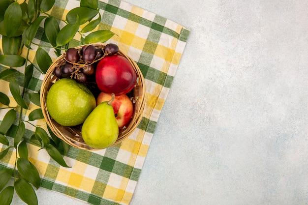 Vista dall'alto di frutti come pera mela pesca uva nel carrello con foglie su un panno plaid e sfondo bianco con spazio di copia Foto Gratuite