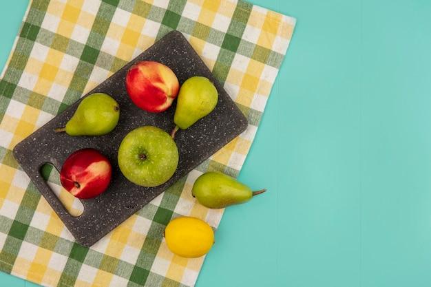 Vista dall'alto di frutti come pera pesca mela sul tagliere con il limone sul panno plaid su sfondo blu con copia spazio Foto Gratuite