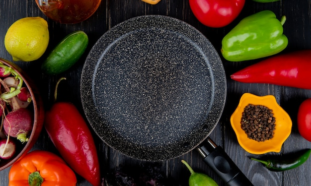 Top view of frying pan and fresh vegetables colorful bell peppers tomatoes radish cucumbers and black peppercorns arranged around on dark wooden table Free Photo