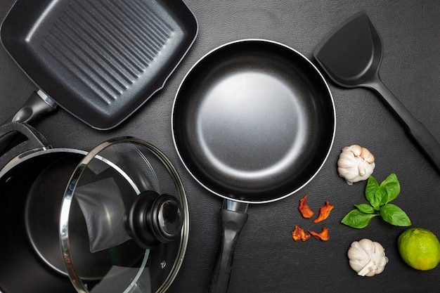 Top view frying pan and pot on black leather background Premium Photo