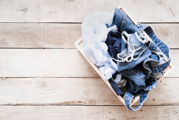 Top view full laundry basket with wooden background Free Photo