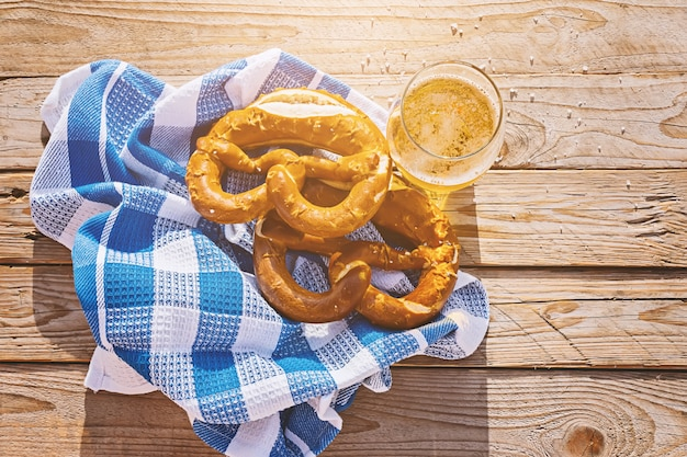 Top view on german pretzel and glass of beer in sun Premium Photo