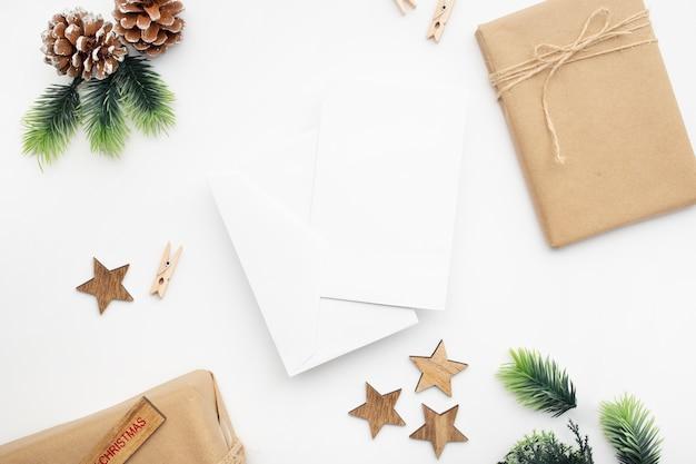 Vista dall'alto di confezione regalo, nastro, rami di abete, coni, anice sul tavolo bianco Foto Gratuite