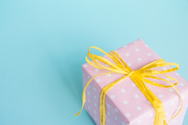Top view of a gift box wrapped in pink dotted paper and tied yellow bow over light blue. Premium Photo