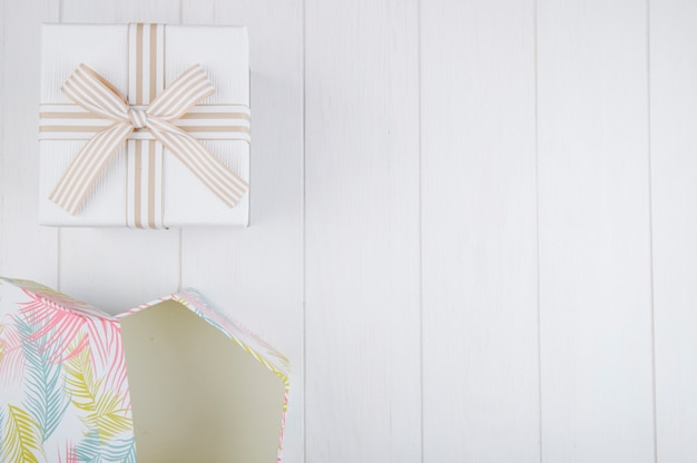 Top view of gift boxes on white wooden background with copy space Free Photo