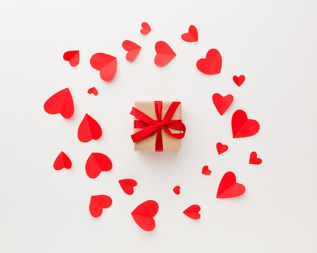 Top view of gift with paper heart shapes Free Photo