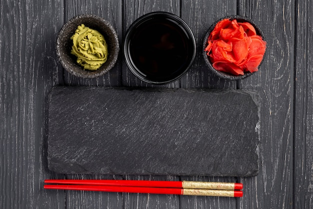Top view ginger wasabi and soy sauce bowls and chopsticks Free Photo